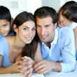 Portrait of happy family laying down bed — Stock Photo #13937284