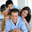 Stock Photo: Portrait of happy family laying down bed