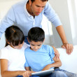 Father controlling children while playing on tablet — Stock Photo #13937377