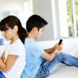 Kids playing at home with smartphones - Stok fotoğraf