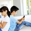 Kids playing at home with smartphones -  