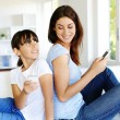 Mother and daughter using mobile phone at home — Stock Photo #13937389