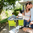 Foto Stock: Family cooking meat on barbecue grill