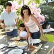 Father serving grilled meat to family — Stock Photo