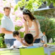 Mother serving lunch to kids in home garden — Stock Photo