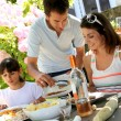 Father serving grilled meat to family — Stock Photo #13937420