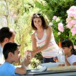Stock Photo: Woman serving water to family having lunch