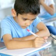 Closeup of young boy writing on notebook at school — Stock Photo