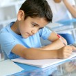 Closeup of young boy writing on notebook at school — ストック写真 #13937454