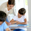 Teacher helping young girl in class with lesson — Stock Photo #13937480