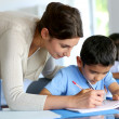 Teacher helping young boy with writing lesson — Stock Photo