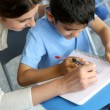Teacher helping young boy with writing lesson — ストック写真 #13937493