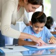 Teacher helping young boy with writing lesson — Stock Photo #13937497