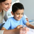 Teacher helping young boy with writing lesson — Foto Stock