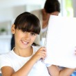 Closeup of beautiful school girl showing notebook page — Stock Photo #13937567