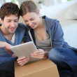 Young couple using tablet to find transport company — Stock Photo