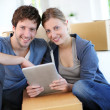 Young couple using tablet to find transport company — Stock Photo #13938445