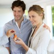 Happy young couple getting keys of their new home — Stock Photo #13938464