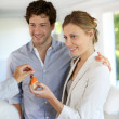 Happy young couple getting keys of their new home - Stok fotoğraf