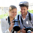 Couple of photographers looking at snapshots — Stock Photo