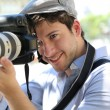 Portrait of young photographer holding camera — Stock Photo