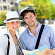 Trendy young couple in town with touristic map — Stock Photo #13938574