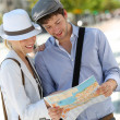 Trendy young couple in town with touristic map — Stock Photo