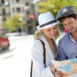 Trendy young couple in town with touristic map — Stockfoto #13938578