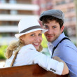 Lovely young couple sitting on public bench — Stock Photo