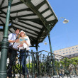 Young couple standing in gazebo reading touristic map — Stock Photo