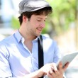 Young man with hat using digital tablet in town — 图库照片