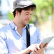 ung man med hatt med digital Tablet PC i stan — Stockfoto