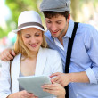 Stock Photo: Young couple in town using electronic tablet