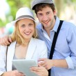 Young couple in town using electronic tablet — Stock Photo #13938630