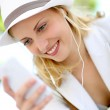 Attractive young blond girl using smartphone — Stock Photo