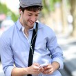 Stock Photo: Young trendy guy talking on mobilephone in street