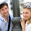 Portrait of cheerful couple standing by lamppost in town — Stock Photo #13938697