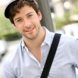 Closeup of young cheerful man wearing hat — Stock Photo
