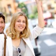Stock Photo: Young couple hailing for taxi cab