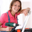 Woman standing on scale with electric drill - Foto de Stock