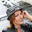 Portrait of woman with hat and leather jacket in town — Stock Photo