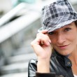 Portrait of woman with hat and leather jacket in town — Stock Photo #13939119