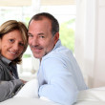 Portrait of happy senior couple sitting in sofa — Stock Photo #13939732