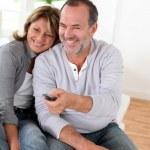 Senior couple watching televion at home — Stock Photo