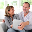 Senior married couple choosing movie on tv — Stock Photo