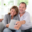 Stock Photo: Senior married couple choosing movie on tv