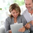 Senior couple using credit card to shop online — Stock Photo #13939818