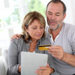 Senior couple using credit card to shop online — Stock Photo