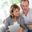 Senior couple using credit card to shop online — Stock Photo #13939827