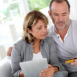 Stock Photo: Senior couple using credit card to shop online